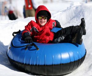 A child on a blue snow tube slides down the hill
