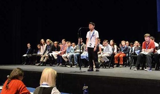 Students on a stage during a spelling bee competition.