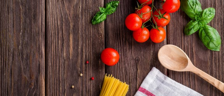 Tomatoes, pasta and utensils on a wooden cutting board.