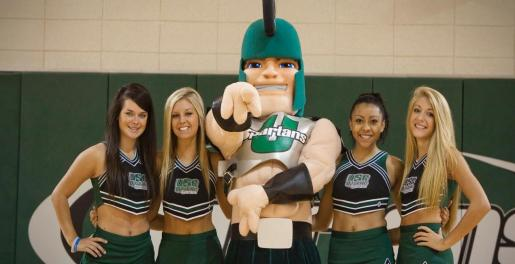 The USC Upstate mascot posing with cheerleaders in the USC Upstate gym.